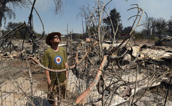 James McCauley looks over the burned-out remains of his residence in the town of Lower Lake, Calif.