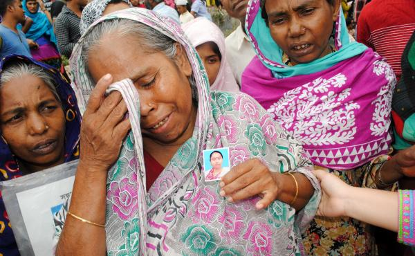 Two years after the collapse of the factory at Rana Plaza, families of victims gather, holding photos of their lost loved ones.