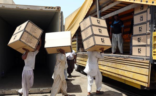 Iranian workers transfer goods from a cargo container to trucks in May at the Kalantari port in Chabahar, Iran. The removal of sanctions on Iran under a recent deal with world powers is expected to boost the country's economy, but the agreement was carefu