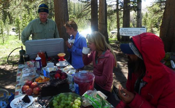 Hank Magnuski (left) feeds hikers at his pop-up Sonora Pass Cafe. Some of his diners also took the opportunity to use his wi-fi.