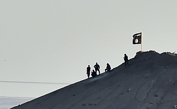 Alleged Islamic State militants stand next to an ISIS flag atop a hill in the Syrian town of Ain al-Arab, called Kobane by the Kurds, as seen from the Turkish-Syrian border in Suruc, Turkey, on Monday.