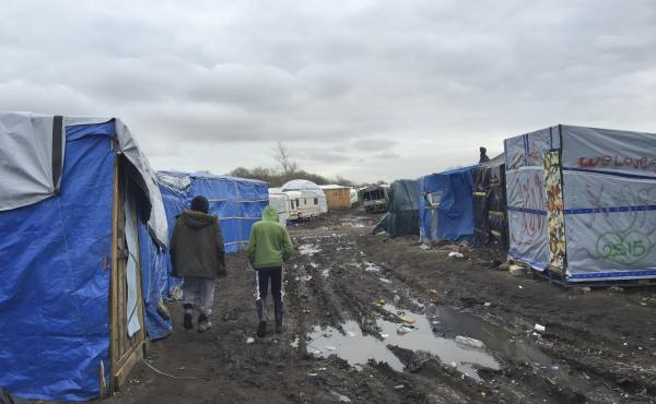 """Amran, an unaccompanied minor from Afghanistan, at right, walks in the camp known as the Jungle with 35-year-old Farid Hamdan, a father of four, also from Afghanistan. """"My heart is saying help him because he's only a kid,"""" says Hamdan. """"He has nobody else"""