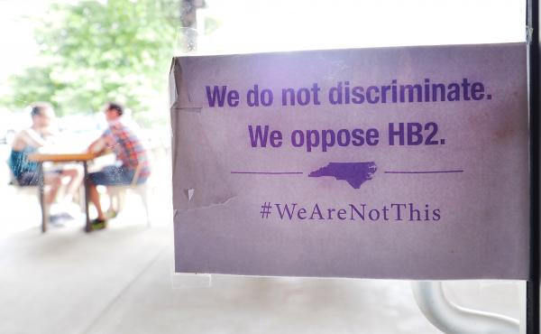 "The ""We Are Not This"" slogan is posted at the entrances to Bull McCabe's Irish Pub in May 2016 in Durham, North Carolina. The sign is protesting a law that has been in place for a year now; the AP estimates it will cost the state some $3.7 billion in busi"