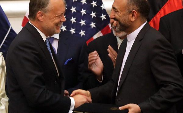 Afghan National Security Adviser Mohammad Hanif Atmar (right) and U.S. Ambassador to Afghanistan James Cunningham exchange documents after signing the Bilateral Security Agreement, with Afghan President Ashraf Ghani (rear, left) and Chief Executive Abdull