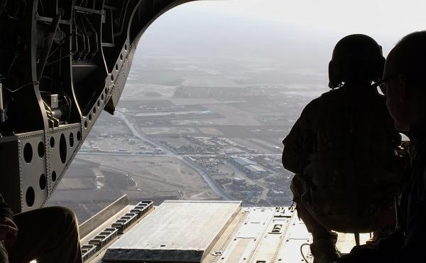 One of the 8,400 remaining U.S. troops in Afghanistan guards the bay of a CH-47 Chinook transport helicopter as it flies near Kabul.
