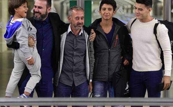 Syrian refugee Osama Abdul Mohsen (middle) is greeted as he arrives in Madrid in September with sons Zaid (far left) and Mohammad (second from right). Abdul Mohsen was tripped by a camerawoman as he scrambled across a field on the Serbia-Hungary border la
