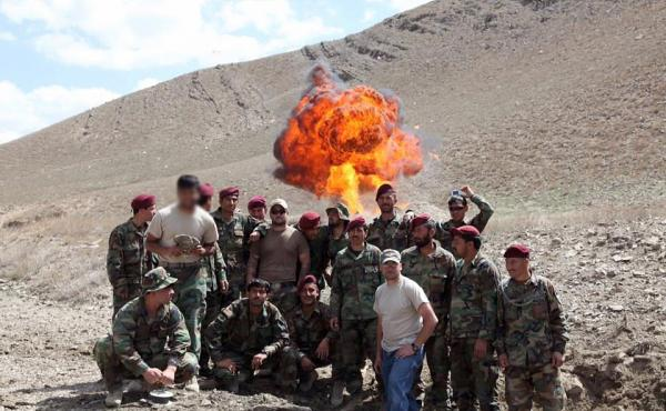 AK, in a tan T-shirt on the left, his face blurred for his protection, was an Afghan interpreter who worked for the U.S. military. He poses with Afghan commandos in front of a controlled explosion. AK worked closely with American Jonathan Schmidt, in the