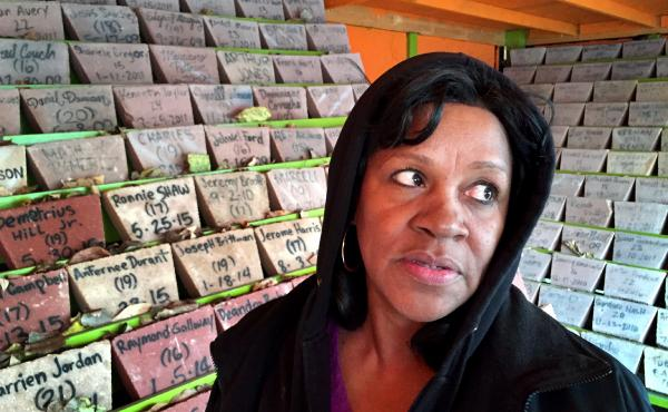 Anti-violence activist Diane Latiker stands before the memorial for young people lost to violence in Chicago over the last several years. More than 500 stones honor the victims and there are hundreds more that still need to be added.