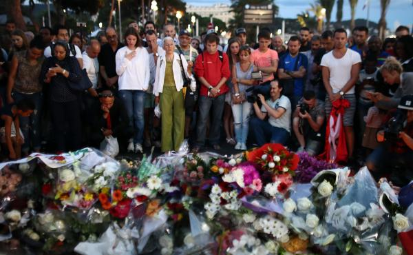 People gather and lay flowers on Nice's Promenade des Anglais on July 15. A French-Tunisian attacker left 84 people dead after driving a truck through crowds gathered to watch fireworks during Bastille Day celebrations. The attacker then opened fire on th