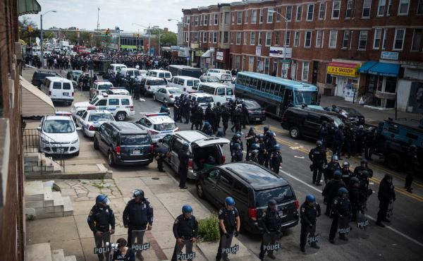 Police stand guard as people protest near a CVS that was set on fire Monday during rioting after Gray's funeral. Baltimore police Capt. Eric Kowalczyk said at least 235 people have been arrested, 34 of them juveniles.