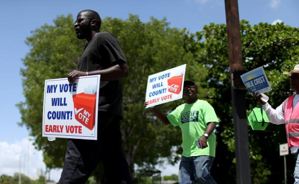 Voters walk to an early voting site to cast their ballots on Aug. 11 in Miami. On Wednesday, a federal appeals court in Ohio upheld a decision extending early voting in that state. Meanwhile, as Election Day nears, courts are still considering cases about