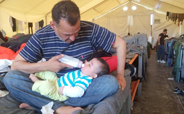 Moyaad Saad, a 43-year-old former civil servant from Baghdad, feeds his 6-month-old daughter Zahara on their cot in a giant tent at a makeshift migrant camp near the border between Greece and Macedonia. Thousands of asylum seekers are now stuck here after