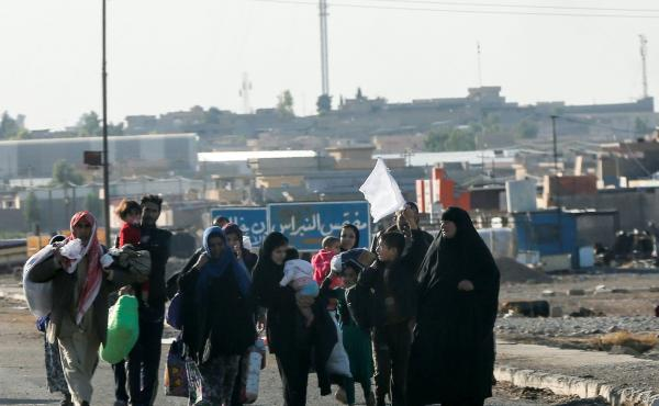 Iraqis living east of Mosul hold a white flag as they flee Wednesday during an Iraqi army's operation to retake the ISIS-held city. So far, the number of civilians fleeing the fighting has been relatively small. But aid groups warn the numbers could rise
