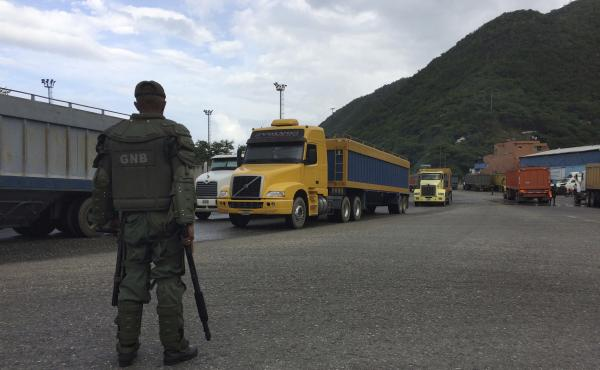 A Venezuelan soldier watches over cargo trucks leaving the port in Puerto Cabello, which handles the majority of the country's food imports. Across the chain of command, from high-level generals to the lowest foot soldiers, military officials are using th