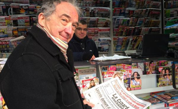 Frenchman Jean Yves Boyer buys a copy of the French weekly Le Canard Enchainé, which marks its 100th anniversary this year. It sells 400,000 copies a week and is profitable, though it has no advertising and just a bare-bones webpage.