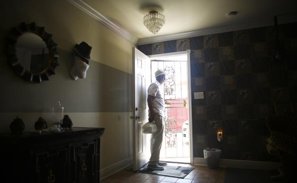 Johnny Jackson looks out the back door of his home as he talks to his neighbors in New Orleans. Jackson's home is still under construction 10 years after Hurricane Katrina nearly destroyed his property.
