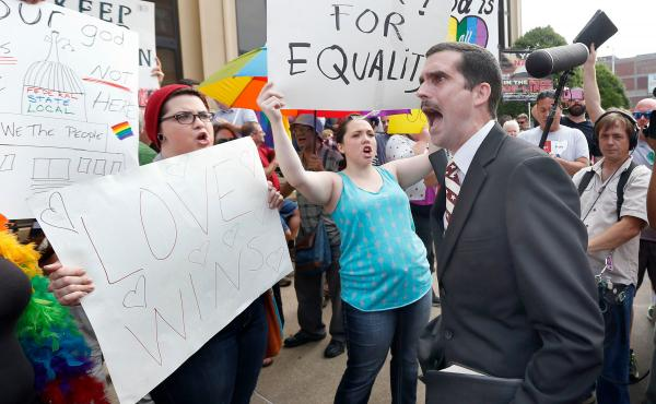 Street preacher Jeffrey Shook, with Unity Baptist Church in Hickory N.C., preaches to Kim Davis protesters in front of the Carl D. Perkins Federal Building in Ashland, Ky., Thursday. Same-sex couples in Rowan County began marrying Friday — but Davis' la