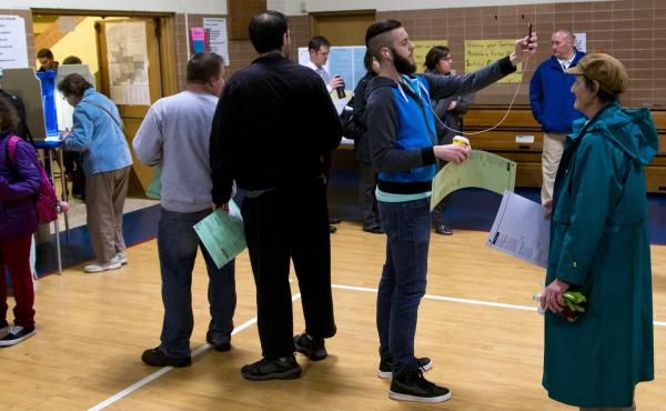 "A man takes a ""selfie"" while waiting in line to cast his vote in the Wisconsin gubernatorial race in November."