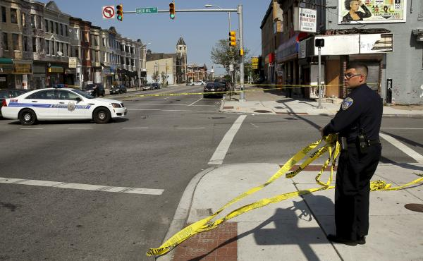 A Baltimore police officer attempts to secure a crime scene with tape at the scene of a shooting at the intersection of West North Avenue and Druid Hill Avenue in West Baltimore, Md., on May 30. Local media have reported more than 35 murders in the city s