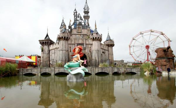 A glitched Little Mermaid piece sits in front of a dismal castle as part of the artist Banksy's biggest show to date, titled Dismaland, at Tropicana in Weston-super-Mare, England.