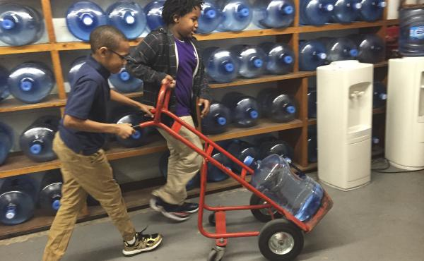 Third-graders Ezekiel White (right) and Emanuel Black push a jug of water to the cafeteria at Southwest Baltimore Charter School.