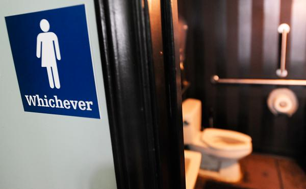 A gender neutral sign is posted outside a bathrooms at Oval Park Grill in Durham, North Carolina.