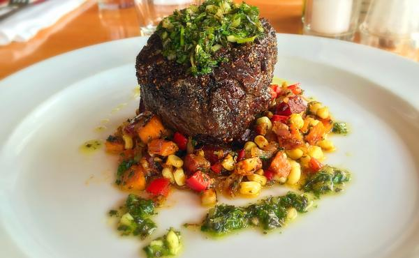 Pan-seared buffalo tenderloin with a corn and sweet potato hash and chimichurri sauce is served up at The Local, a restaurant in Jackson, Wyo.