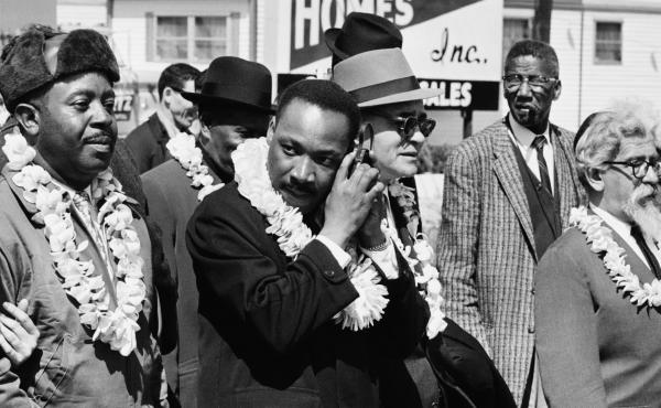 Martin Luther King, Jr. listening to a transistor radio in the front line of the third march from Selma to Montgomery, Alabama, to campaign for proper registration of black voters, March 23, 1965. Ralph Abernathy (second from left), Ralph Bunche (third fr