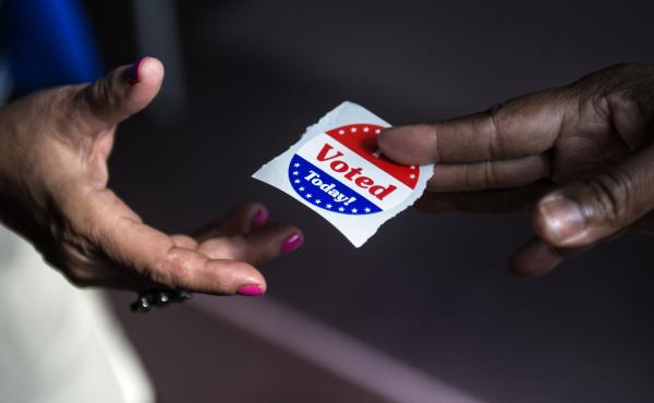 "A poll worker hands out ""I Voted Today"" stickers in Washington, D.C., in 2012. Journalist Ari Berman says a 2013 Supreme Court ruling opened the door for new voting restrictions that  disproportionately affect poor people, young people and people of color"