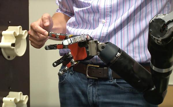 """Each time a particular finger on a robotic hand is touched, a blindfolded Nathan Copeland """"feels"""" as if his own finger were being touched, thanks to a brain implant. That sort of sensory feedback could help him hold a fragile object without crushing it."""