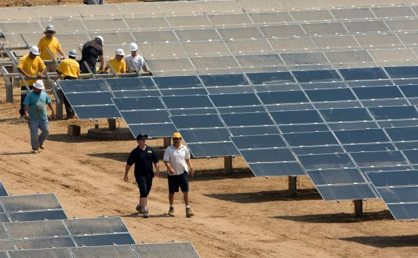 Workers install a solar farm outside Sacramento, Calif. The state aims to attain half of its electricity from renewable sources by 2030.