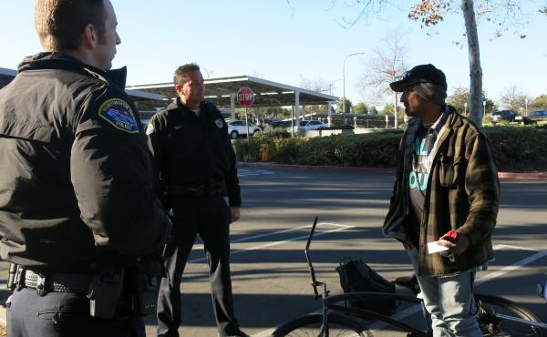 Officers Colin Lewis and Brad Smith (center) on patrol near a park in Huntington Beach, Calif. The area has seen a sharp increase in homelessness and petty thefts, which the officers blame on Proposition 47. But the law's supporters say other California c