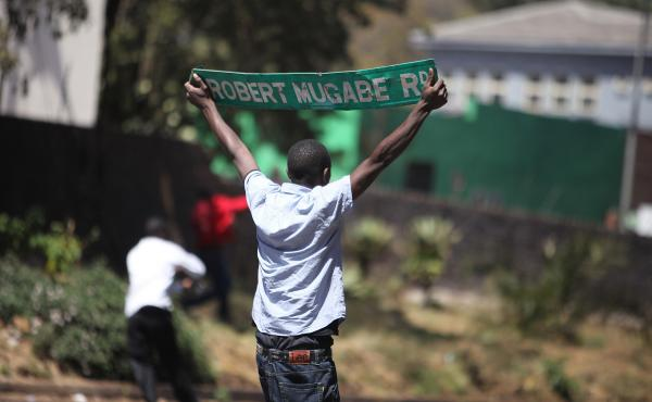 A protester holds up a street sign with President Robert Mugabe name on it as Zimbabwe opposition supporters clash with police during a protest march for electoral reforms on August 26, 2016 in Harare. Riots erupted in Zimbabwe's capital Harare after poli