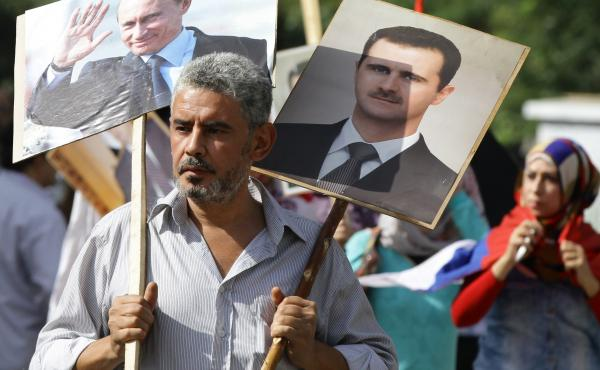 A Syrian man holding portraits of President Bashar Assad and Russian leader Vladimir Putin joins several hundred pro-government demonstrators near the Russian embassy in Damascus on Tuesday to express support for Moscow's air war in Syria. Two rockets lat