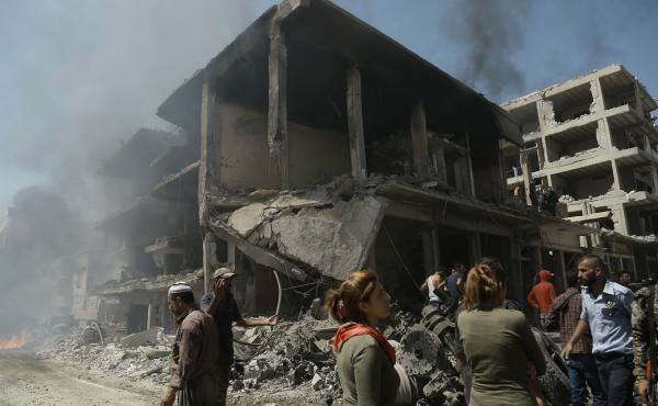People gather at the site of a bombing in Syria's northeastern city of Qamishli Wednesday. The powerful explosion killed at least 44 people and devastated nearby buildings.