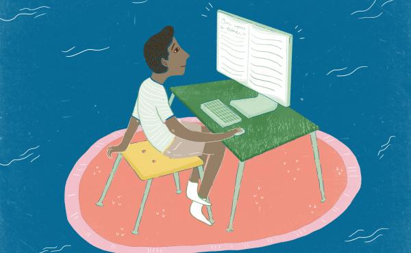 Young man sits in front of computer reading the screen which is made of book pages.