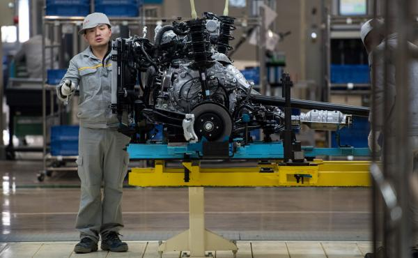 A Chinese worker checks part of a car at the production line of France's Renault and China's Dongfeng Group factory in February.