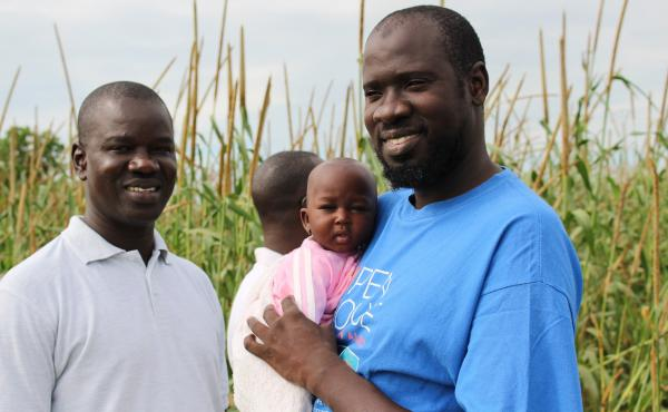 Ousmane Ndiaye loves computer models, climate forecasting and babies. Here he holds farmer Mariami Keita's 4-month-old baby girl, Ndeye.