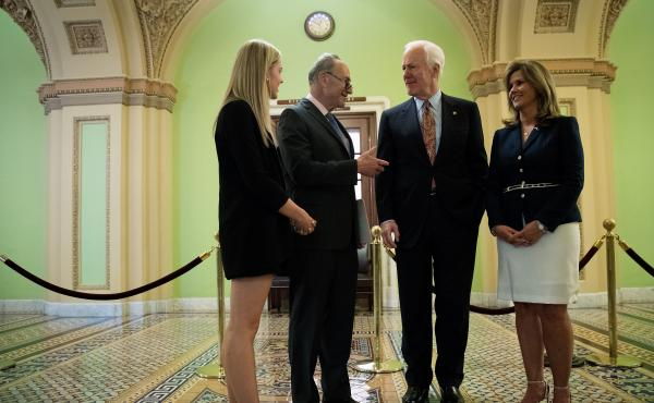 Sens. Chuck Schumer, D-N.Y., and John Cornyn, R-Texas, speak with Kaitlyn (left) and Terry Strada — whose husband, Thomas, died in the Sept. 11 attacks — after a May 17 news conference concerning the Justice Against Sponsors of Terrorism Act in Washin
