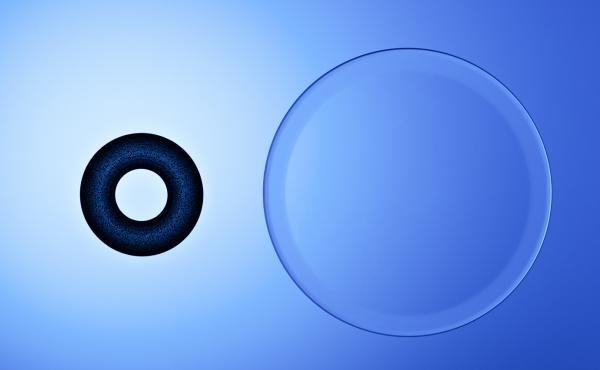 A corneal inlay next to a contact lens.