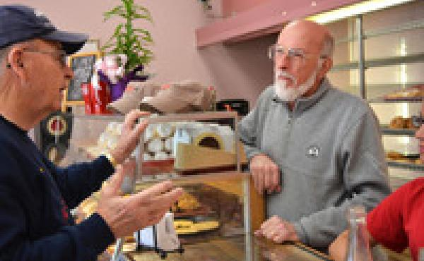 Michael Doucleff Sr. (right) talks to a longtime customer at Duke Bakery in Alton, Ill.
