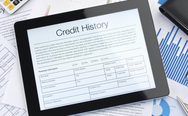 A credit history form appears on a tablet screen sitting on top of paperwork.