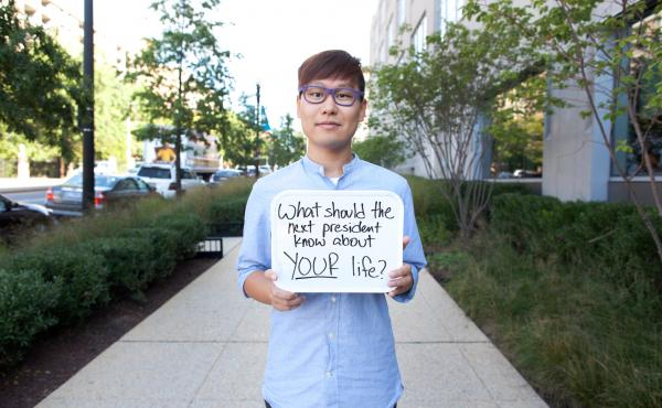 NPR's Wei Quan holds a sign prompting people to respond to the #DearWashington social media conversation about what issues the next president should know about this election season.