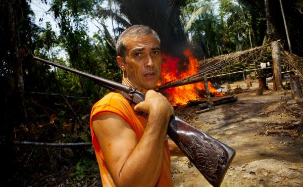 Elizeu Berçacola surveys the scene after he and his fellow rubber tappers set afire one of three illegal logging camps.