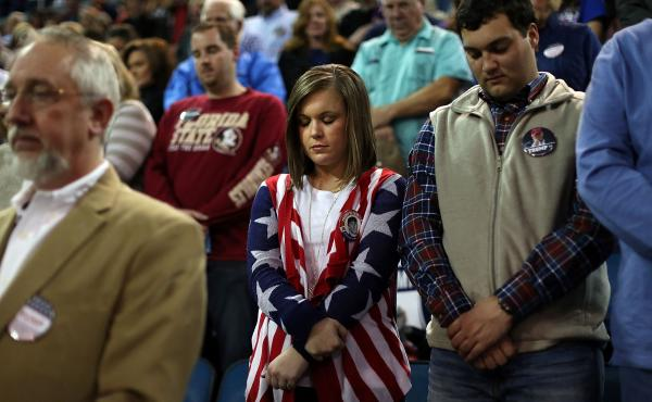 Donald Trump supporters pray while waiting to hear him speak at a campaign event in Mississippi.