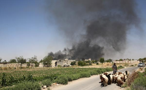 A young Syrian shepherd leads his flock on Tuesday as smoke billows from a farm following a reported airstrike in Sheifuniya, near the rebel-held town of Douma, east of Damascus.