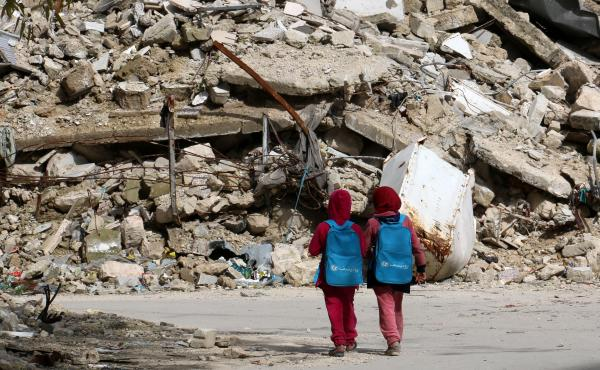 Girls carrying school bags provided by UNICEF walk past destroyed buildings on their way home from school on March 7 in the rebel-held al-Shaar neighborhood of Aleppo, Syria. So many people have fled the city and so much of its infrastructure has been des