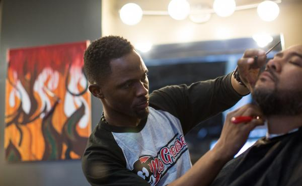Owner of No Grease Barber Shop in Charlotte, N.C., Damian Johnson, finishes up a haircut on Sam Chaney. Sam has been a client for over 10 years.