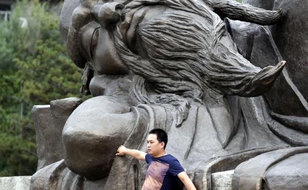 Not exactly what that's for: Two tourists climb on a statue in Huayin, China, near Huashan, or Mount Hua, a famed tourist destination, in May 2013.