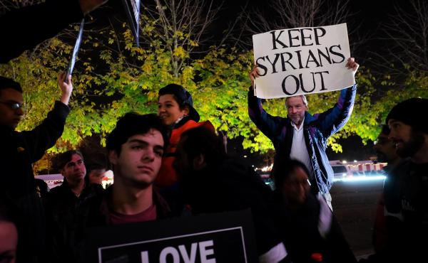 """A counterdemonstrator holds a sign during a gathering in New York City to show solidarity with Syrian and Iraqi refugees last year. Donald Trump's hard-line campaign rhetoric singled out Syrian refugees. """"If I win,"""" he told a New Hampshire rally, """"they ar"""